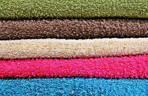A pile of 5 different coloured towels. Colours from top to bottom are: green, brown, beige, pink and blue.