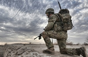 A soldier observes from a compound roof