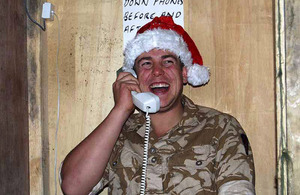 A serviceman on operations in Afghanistan takes time out to call home (stock image)