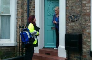An Environment Agency flood support officer talking to a resident at her front door.