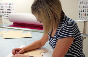woman laying a pattern onto cloth for dressmaking
