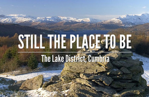 'Still the place to be. The Lake District, Cumbria' text on a winter view of hills and a lake.