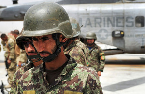 British and Afghan troops wait to board an ISAF helicopter