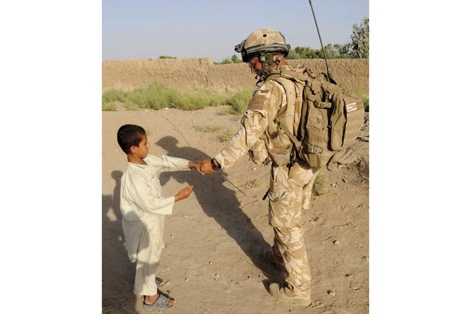 A RAF Regiment Gunner engages with an Afghan child while out on patrol