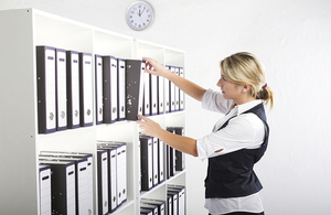 A woman searching files.