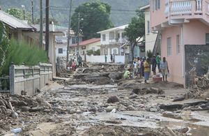 St Lucians carefully negotiate the chaos of rubble, mud and craters where a road ran through this village just days ago