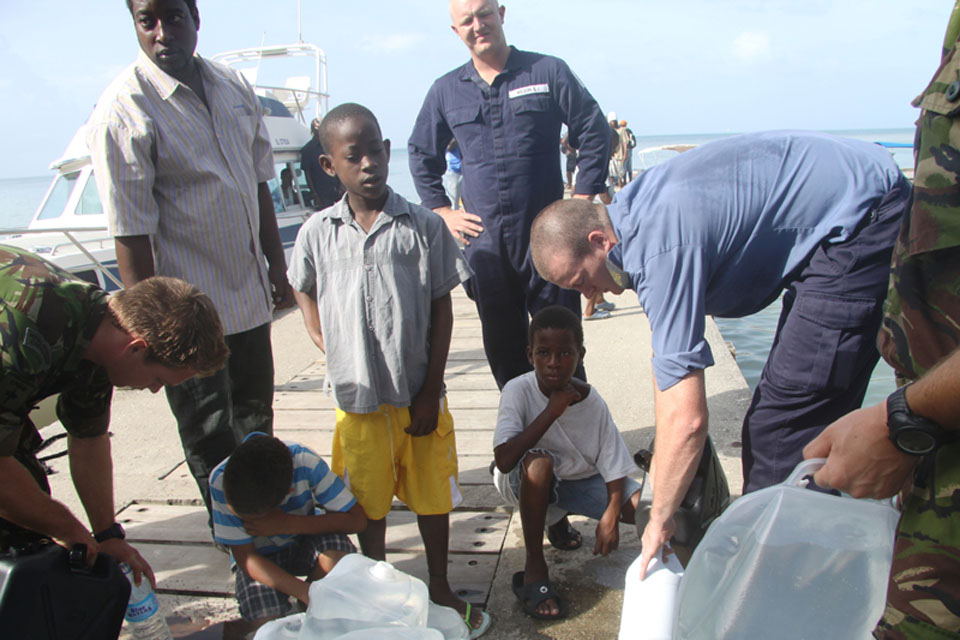 Crew members from HMS Manchester distribute fresh drinking water to locals