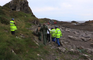 One of the male casualties walks towards HMS Gannet's Search and Rescue helicopter