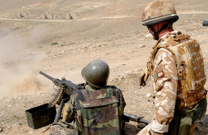 An Afghan infantry instructor being trained in the use of a heavy machine gun by a British advisor