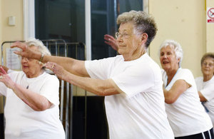 A few elderly women smiling and exercising