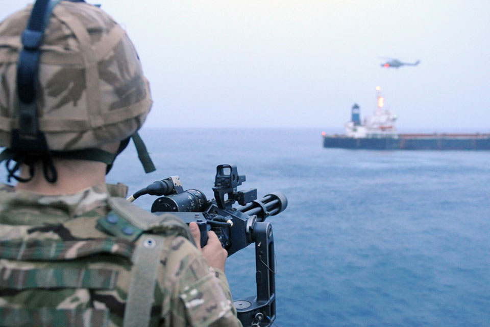 A member of HMS Monmouth's force protection team provides cover during the boarding of the merchant vessel