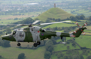 A Lynx helicopter flies over Glastonbury Tor