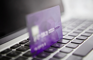 Purple credit card resting on laptop keyboard