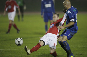Lance Corporal Tony Fitzpatrick (in red) tackles a Sussex player in the Southern Counties Cup football competition at the Aldershot Military Stadium
