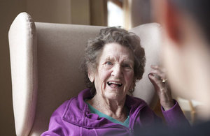 An elderly lady sitting on a chair smiling