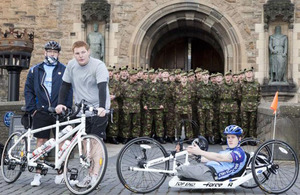 Cyclists Rifleman Michael Paul Jacobs and his brother, and Rifleman Michael Swain, in front of Edinburgh Castle at the start of the Ride of Britain