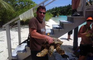 Lieutenant Commander Dan Simmonds handles a hawksbill turtle