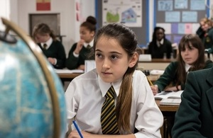 Girl in classroom next to globe.