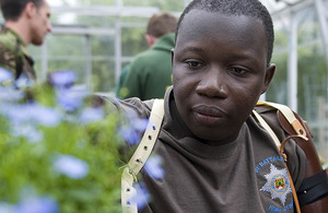 Guardsman Lamin Manneh, 33, from Windsor, originally from the Gambia, and serving with Number 2 Company Irish Guards, tends to plants in the newly-refurbished greenhouse at Headley Court