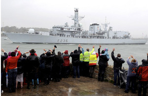 Friends and families wave to their loved ones as HMS Montrose passes Devil's Point