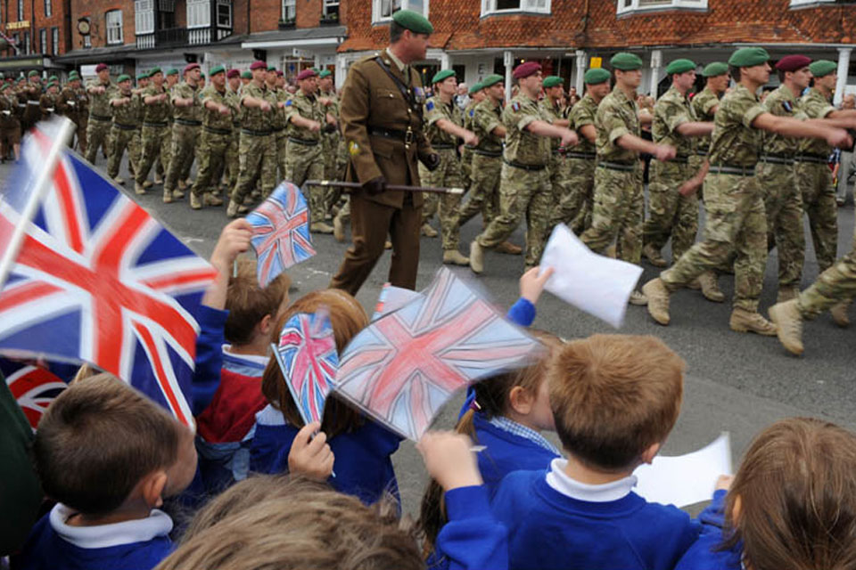 Schoolchildren cheer as soldiers from 4 Military Intelligence Battalion march through the historic Wiltshire town of Marlborough