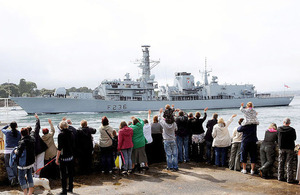 Family and friends wave to the crew of HMS Montrose as the ship leaves HM Naval Base Devonport
