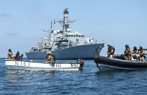 Royal Marines and Royal Navy sailors from HMS Montrose investigate a boat with suspected pirates onboard