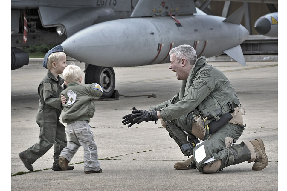 Wing Commander Andy Turk, Officer Commanding IX (Bomber) Squadron, is welcomed home by his sons