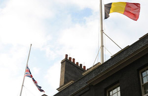 Belgian and UK flags at half-mast