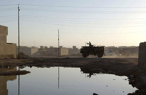 A Saxon amoured personnel carrier provides support to British foot patrols in Basra City in 2003 (stock image)