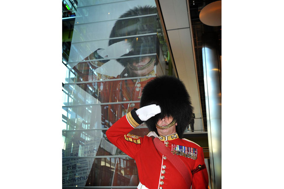 The Garrison Sergeant Major of London District William Mott in front of the picture of himself at London Heathrow's Terminal 5