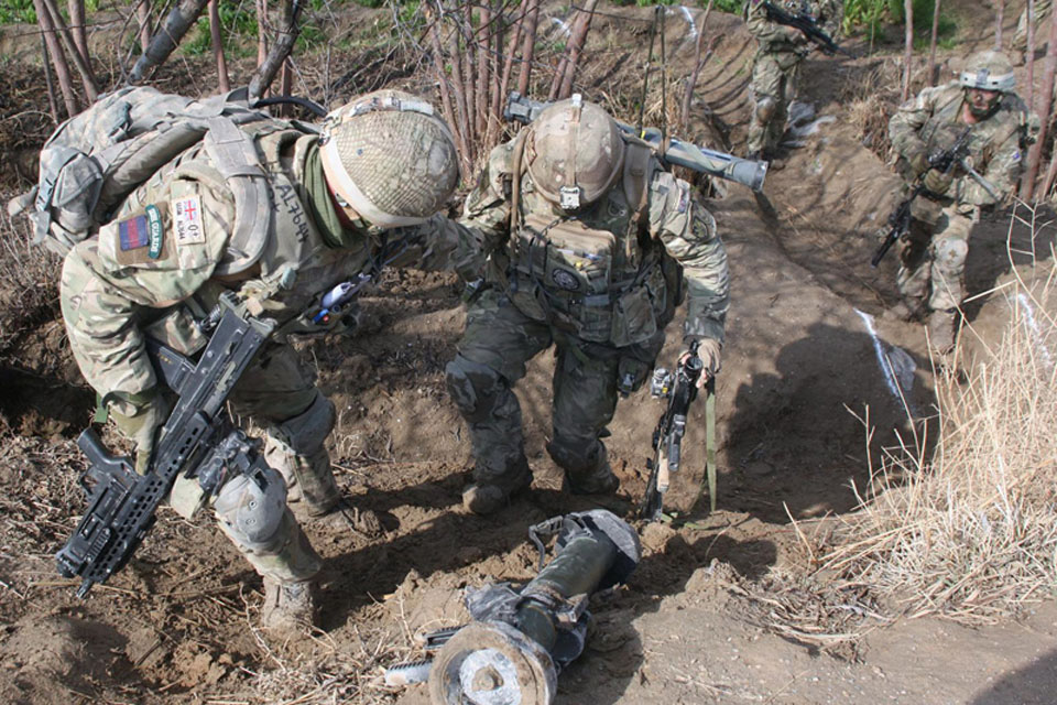 Soldiers from the 1st Battalion Irish Guards negotiate rough terrain during the operation in the town of Pasab