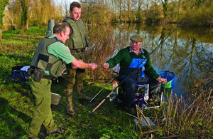 An angler having his rod licence checked by an enforcement team