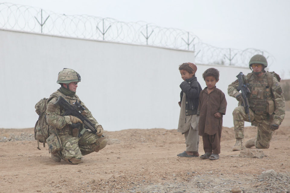 Members of the Irish Guards meet local children outside the school