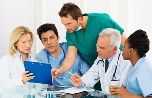 team of medical staff around a table looking at medical charts