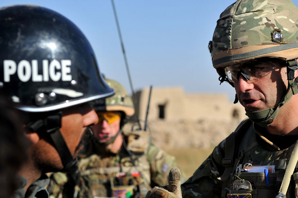 Major Nick Wight-Boycott, Officer Commanding Delta Company, 5th Battalion The Royal Regiment of Scotland, discusses the insurgent threat with an Afghan policeman