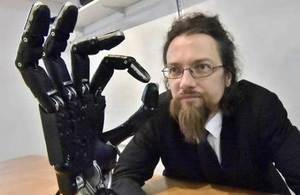 Shadow Robot md Rich Walker with robot hand on desk in foreground
