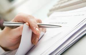 A person reviewing some papers with a pen