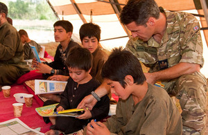 Warrant Officer Taff Davies helps Afghan children with their reading skills