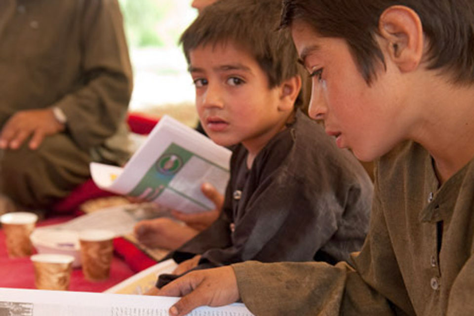 Afghan children using ISAF newspapers printed in Dari, Pashtu and English to improve their reading skills