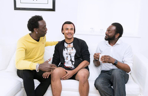 Three men sat on a sofa chatting