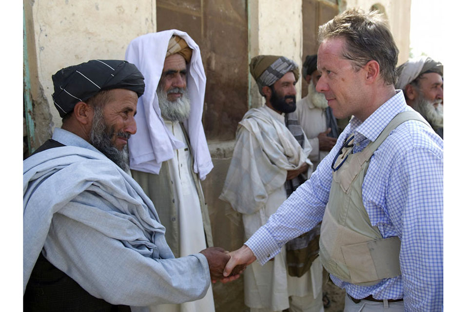 Mr Michael O'Neill greets local Afghans on his arrival at a school they want to rebuild in Naqilabad
