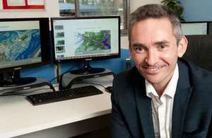 Ambiental CEO Justin Butler in his office with flood mapping imagery on screens in the background
