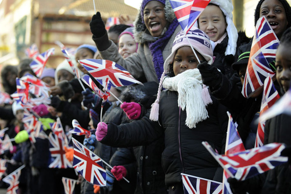 Hundreds of excited schoolchildren, waving flags, lined the streets of Woolwich to watch the parade