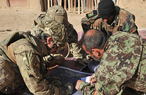 Afghan National Army officers plan which compounds to search with their British advisor prior to one of their most ambitious operations in the boundary areas between the districts of Nad 'Ali, Nahr-e Saraj, and Lashkar Gah