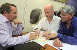 From left: Defence Secretary Dr Liam Fox, Foreign Secretary William Hague, and International Development Secretary Andrew Mitchell talking during a flight to Kabul, Afghanistan