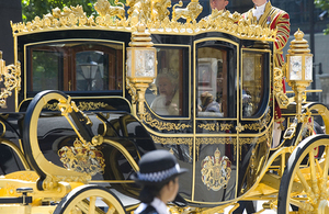 Her Majesty the Queen in a golden carriage.