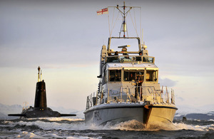 The Royal Navy P2000 patrol vessel HMS Dasher escorts nuclear submarine HMS Vanguard to her berth at HM Naval Base Clyde