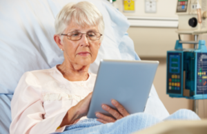 Patient in hospital bed using an iPad