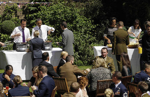 Prime Minister David Cameron, US President Barack Obama, and their wives - Samantha Cameron and First Lady Michelle Obama - serve food to members of the military from the UK and the US during a barbecue in the garden of 10 Downing Street